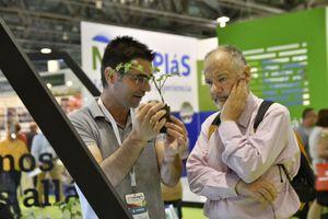 Un miembro del equipo de una empresa expositora en Infoagro Exhibition explica sus productos a un visitante profesional